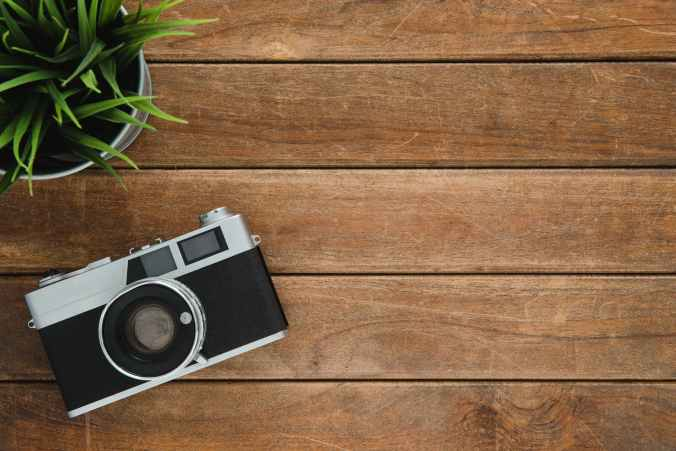 black and silver film camera on brown wooden surface