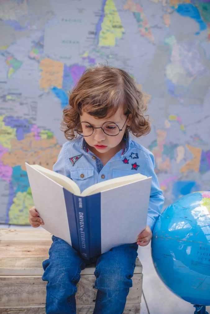 girl reading book while sitting beside desk globe