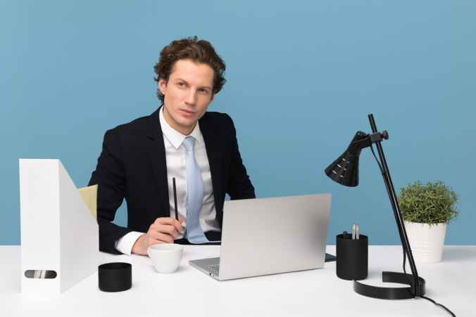 man sitting with laptop computer on desk and lamp