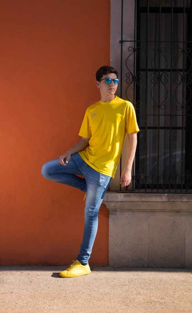 man wearing yellow crew neck t shirt and blue denim jeans