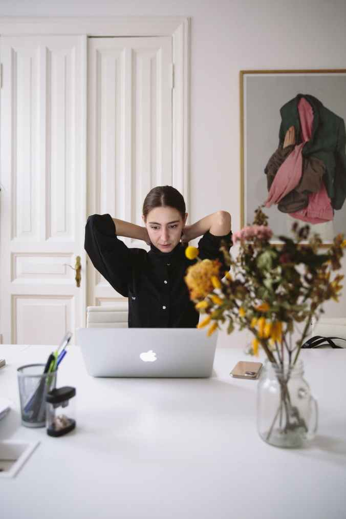 woman in black blouse sitting in front of silver laptop