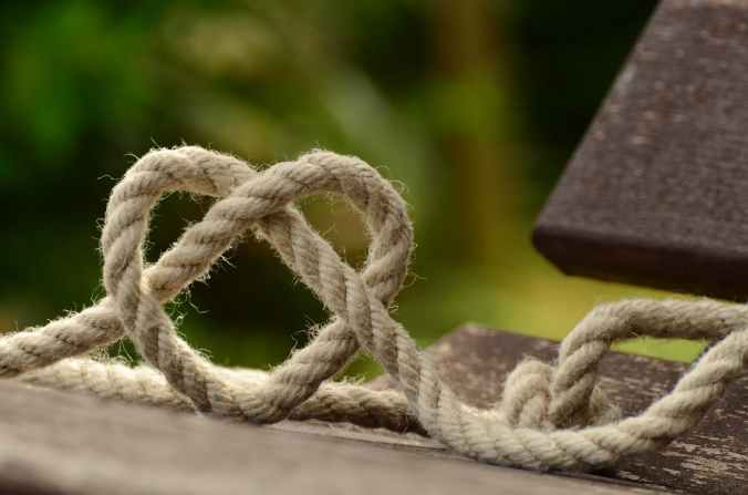 brown rope tangled and formed into heart shape on brown wooden rail